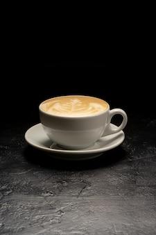 Xícara de cappuccino branca com um padrão clássico. uma xícara de café em uma mesa preta.