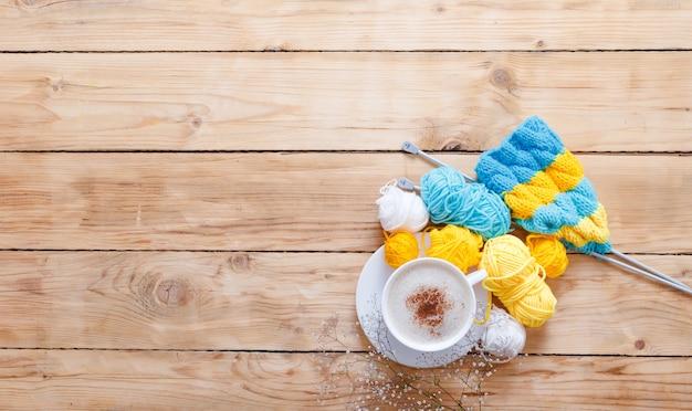 Xícara de cappuccino branca, lenço de malha e fios multicoloridos em uma vista superior de fundo branco de madeira.