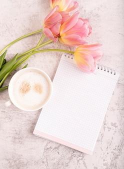 Xícara de cappuccino, caderno e vista superior de tulipas cor de rosa no fundo de mármore