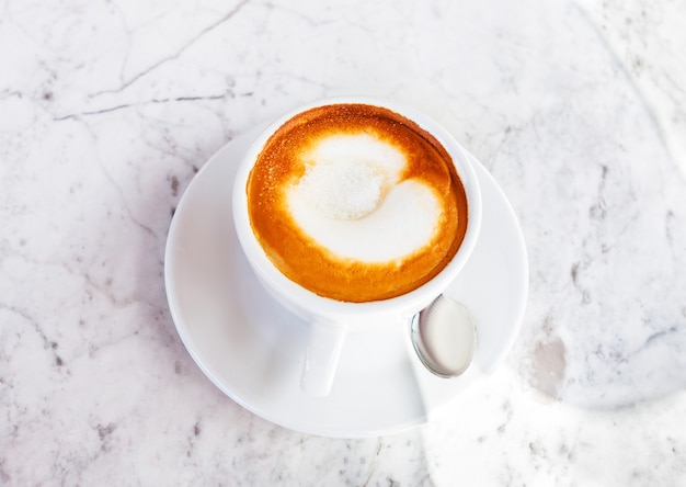 Xícara de cappuccino, café com açúcar em uma mesa de mármore