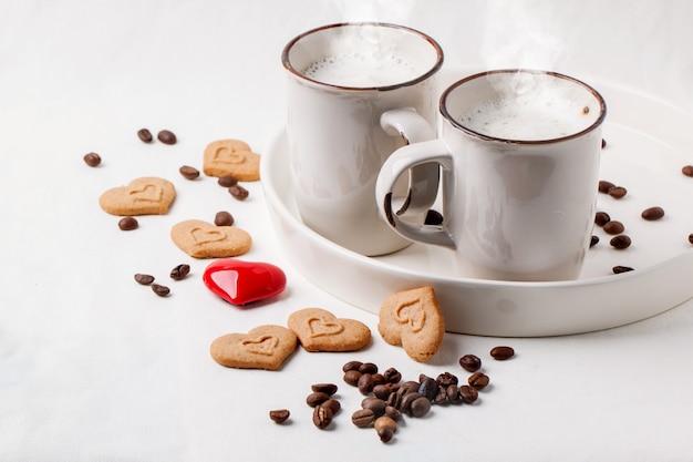 Xícara de cappuccino com biscoitos como corações de reboque