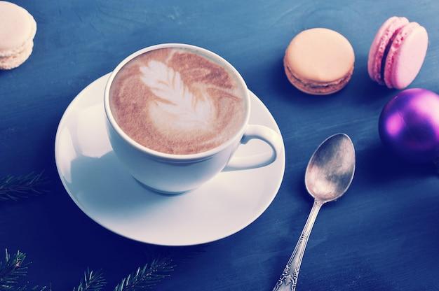 Xícara de cappuccino com bolo macaron, brinquedos de natal