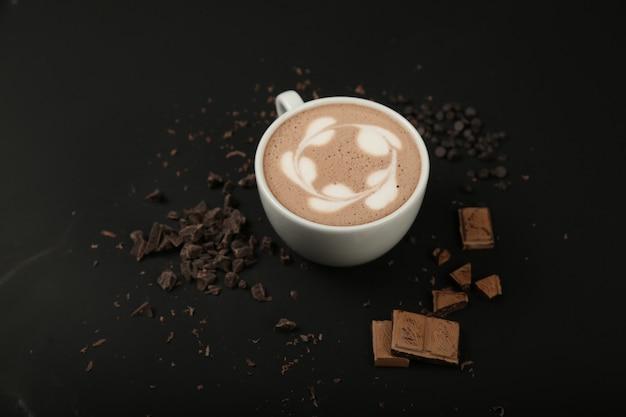 Xícara de cappuccino com chocolate na superfície preta de vista frontal