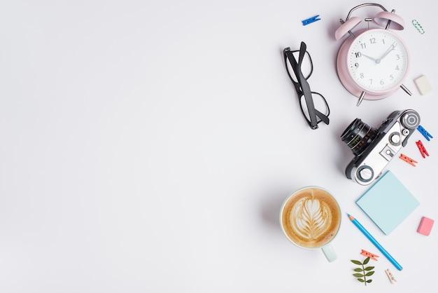 Xícara de cappuccino com latte art; câmera vintage; despertador; lápis e óculos no fundo branco