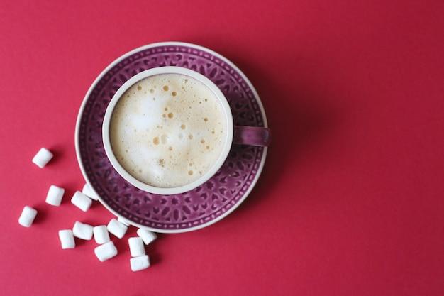 Xícara de cappuccino com marshmallows em fundo vermelho