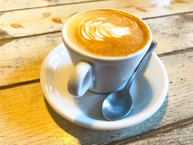 Xícara de cappuccino com padrão na mesa de madeira velha.