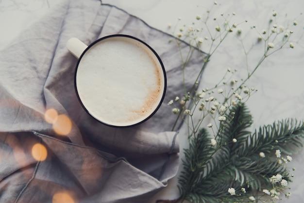 Xícara de cappuccino com ramos de pinheiro e flores de gipsófila luzes quentes bokeh