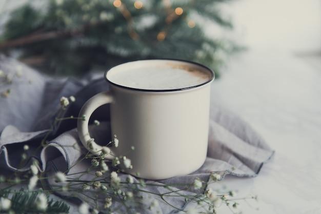 Xícara de cappuccino com ramos de pinheiro e flores de gipsófila