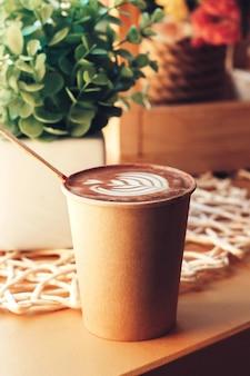 Xícara de cappuccino com um padrão em uma mesa em um café