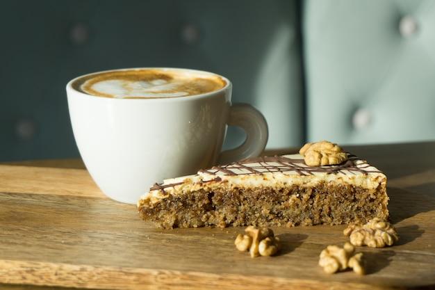 Xícara de cappuccino com um pedaço de bolo