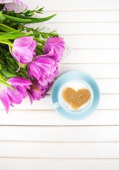 Xícara de cappuccino com um símbolo em forma de coração e tulipas roxas em um fundo de madeira