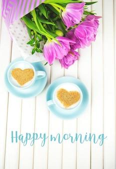Xícara de cappuccino com um símbolo em forma de coração e tulipas roxas