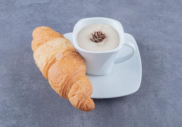 Xícara de cappuccino e croissant no café da manhã em fundo cinza.
