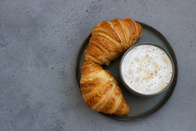 Xícara de cappuccino e dois croissants frescos