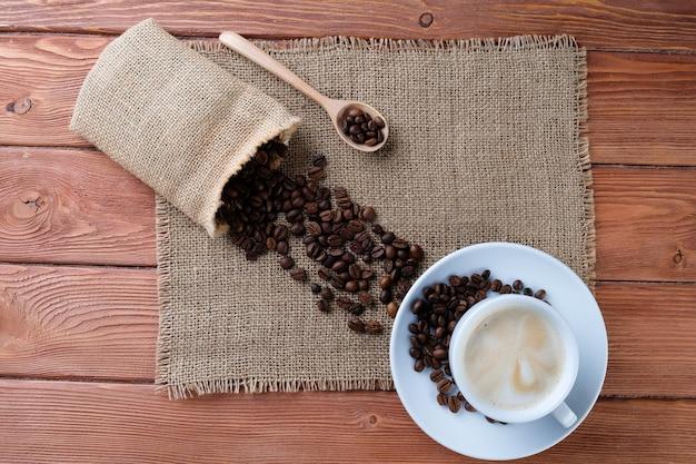 Xícara de cappuccino e grãos de café na mesa