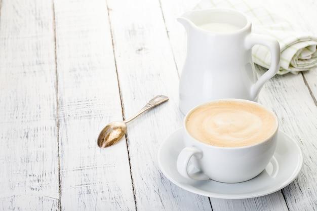 Xícara de cappuccino e jarro de leite na velha mesa de madeira pintada de branco.