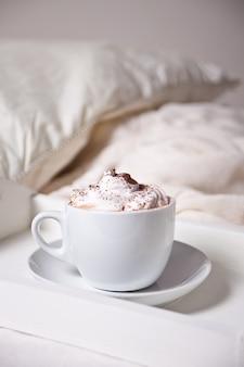 Xícara de cappuccino na bandeja branca na cama de manhã cedo