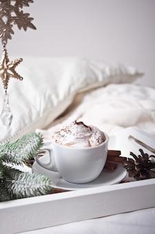Xícara de cappuccino na bandeja branca na cama, manhã de inverno