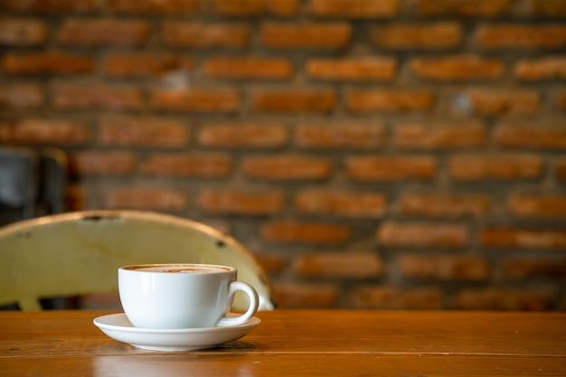 Xícara de cappuccino na mesa de madeira contra a parede de tijolos interna