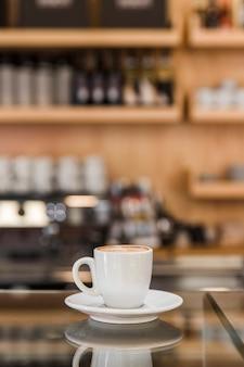 Xícara de cappuccino no balcão de vidro