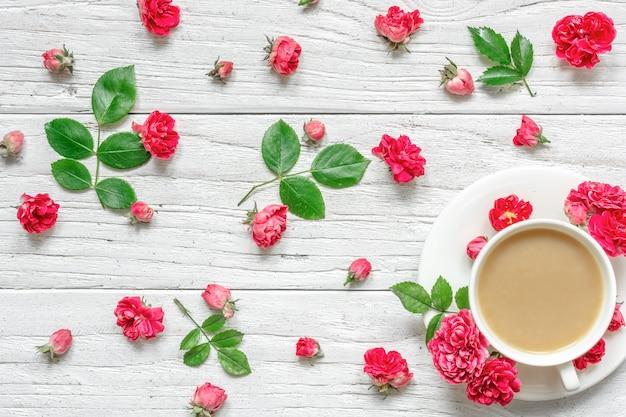 Xícara de cappuccino ou café com leite com composição de flores feita de flores rosas rosa