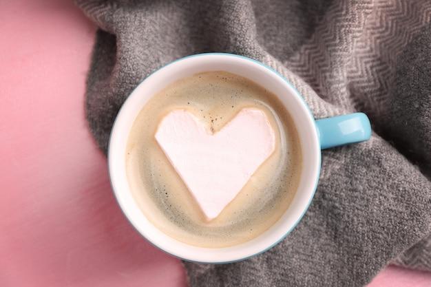 Xícara de cappuccino quente com marshmallow de coração e lenço quente na superfície rosa, close-up