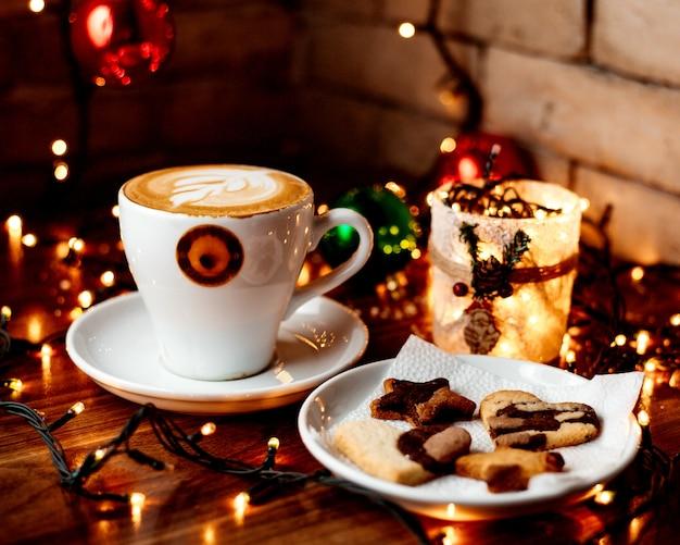 Xícara de cappuccino quente e um prato com biscoitos