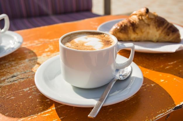 Xícara de cappuccino revigorante e um croissant no café da manhã Foto Premium