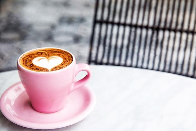 Xícara de cappuccino rosa pastel com coração latte art. café no fundo de mármore com piso ornamental.