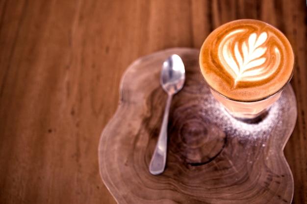 Xícara de cappucino quente está sobre a mesa de madeira