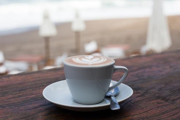 Xícara de cappucino quente no fundo da mesa de madeira com vista para o mar de fundo. conceito de férias.