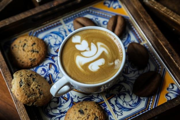 Xícara de capuccino de vista lateral com biscoitos de aveia em uma bandeja