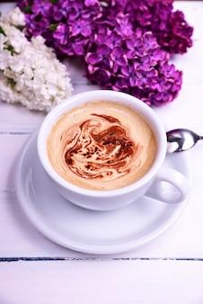 Xícara de capuccino em uma mesa de madeira branca