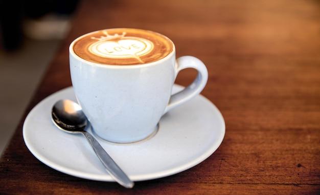 Xícara de capuccino está na mesa de textura de madeira