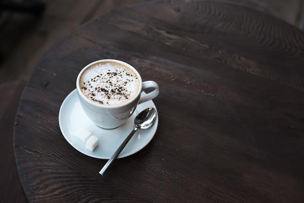 Xícara de capuccino na velha mesa de madeira escura