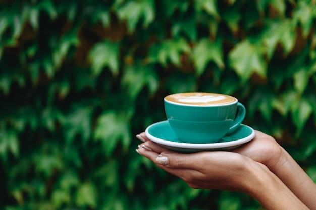 Xícara de capuccino quente na cor turquesa nas mãos da mulher