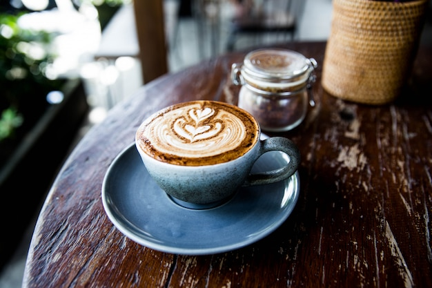 Xícara de capuccino quente na mesa de madeira