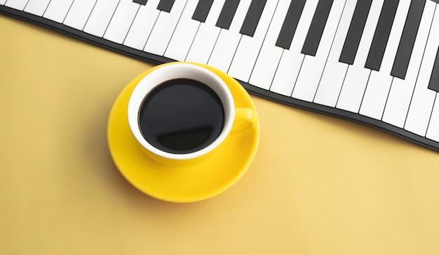 Xícara de cerâmica amarela com café preto colocada ao lado das teclas do piano, fundo pastel