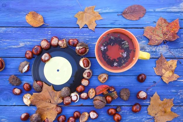 Xícara de cerâmica amarela de chá de ervas e discos de vinil vintage em fundo de madeira envelhecido com castanhas e folhas de outono.