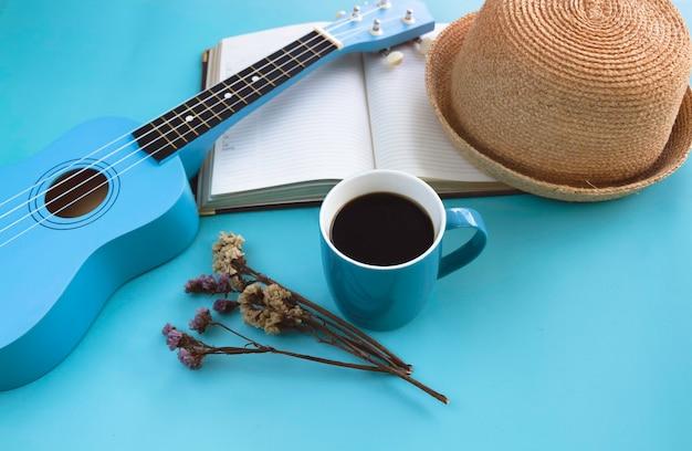 Xícara de cerâmica azul com café preto colocada ao lado de flor seca e ukulele, em fundo pastel