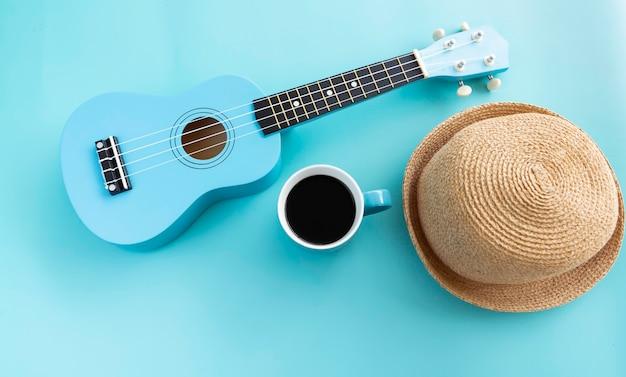 Xícara de cerâmica azul com café preto colocada ao lado do ukulele e chapéu tecido, em fundo pastel