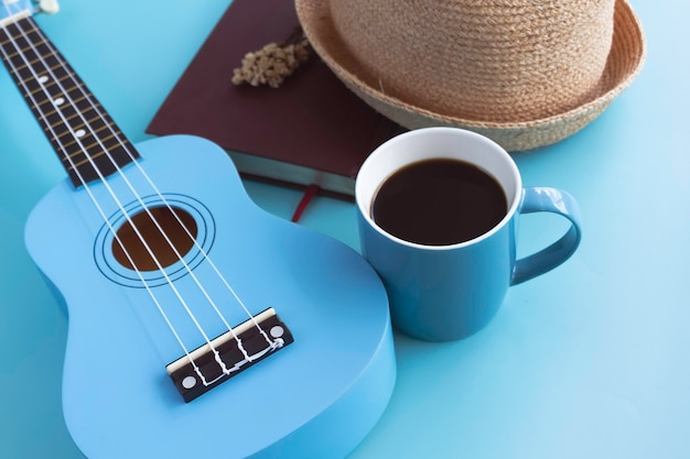 Xícara de cerâmica azul com café preto colocada ao lado do ukulele, em fundo pastel. luz borrada ao redor