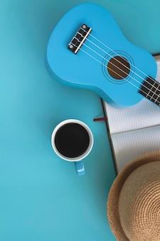 Xícara de cerâmica azul com café preto colocada ao lado do ukulele, livro e chapéu tecido. em fundo pastel