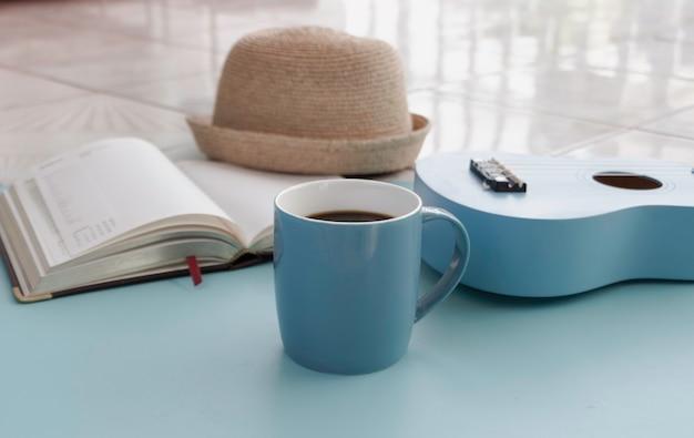 Xícara de cerâmica azul com café preto colocada na frente do ukulele borrado, luz borrada ao redor