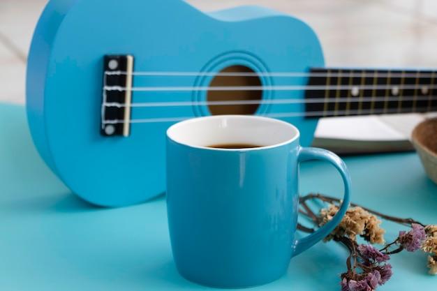 Xícara de cerâmica azul com café preto colocada na frente do ukulele desfocado, em fundo pastel, luz desfocada ao redor