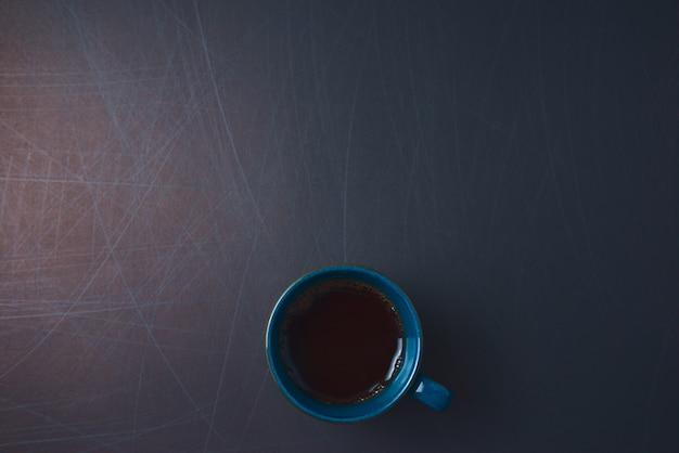 Xícara de cerâmica azul de estilo vintage de café preto quente com espuma dourada em fundo arranhado