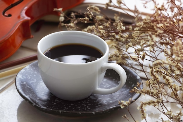 Xícara de cerâmica branca com café preto colocada ao lado de flores desfocadas, no fundo, luz desfocada ao redor