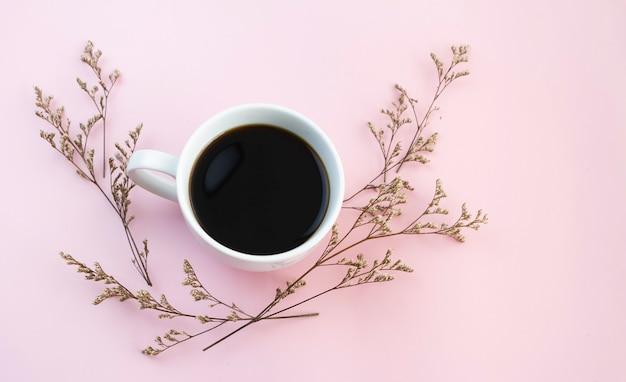 Xícara de cerâmica branca com café preto colocada ao lado de flores secas, em fundo pastel