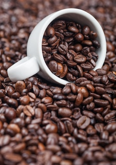 Xícara de cerâmica branca com grãos de café dentro de fundo de grãos de café torrados de aroma fresco. macro