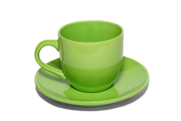 Xícara de cerâmica verde e pires isolados no branco.